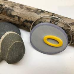Large Yellow and Grey Fibula Brooch by Bronwen Gwillim with pebbles and piece of driftwood